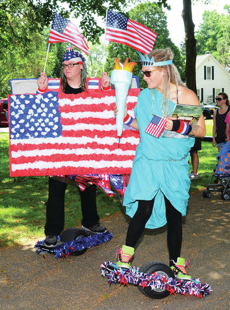 Mike Ullery   Daily Call Patriotic husband and wife team Jaymie and Josh Bryant of Piqua are decked out from the tops of their heads to the bottom of their off-road hoverboards as they participate in Tuesday's Piqua 4th Fest event at Fountain Park.
