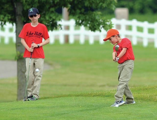 Mike Ullery | Daily Call Chris Galbreath, 9, hits an approach shot as his brother Matthew, 12, watches during Echo Hills Junior Golf Camp recently.