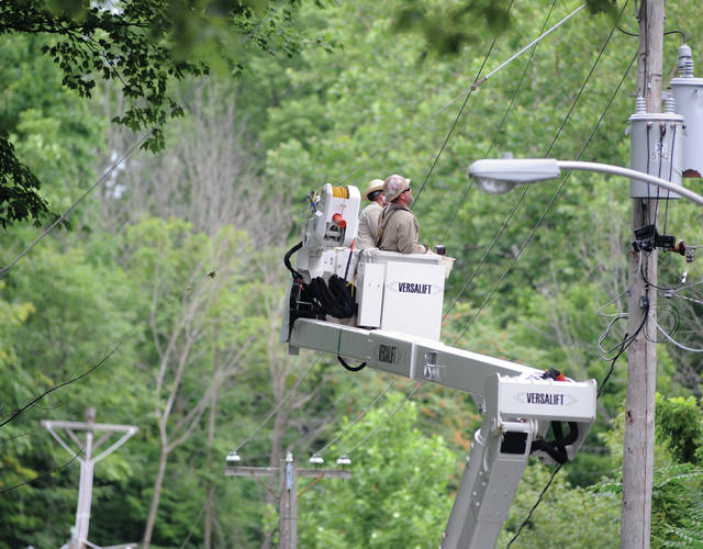 Workers from Piqua Power check out an issue with power lines at Hollow Park on Wednesday. The steep hill put the bucket at nearly eye level with the camera.