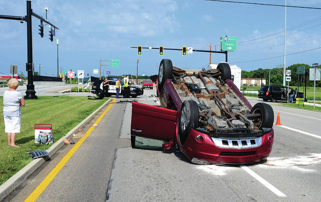 Mike Ullery | Daily Call Piqua police investigate a two-vehicle crash on East Ash Street at I-75 on Friday morning. The crash left on vehicle on its top and the other with heavy damage. Fortunately, there were no injuries in the 10 a.m. crash but traffic was tied up for nearly an hour.