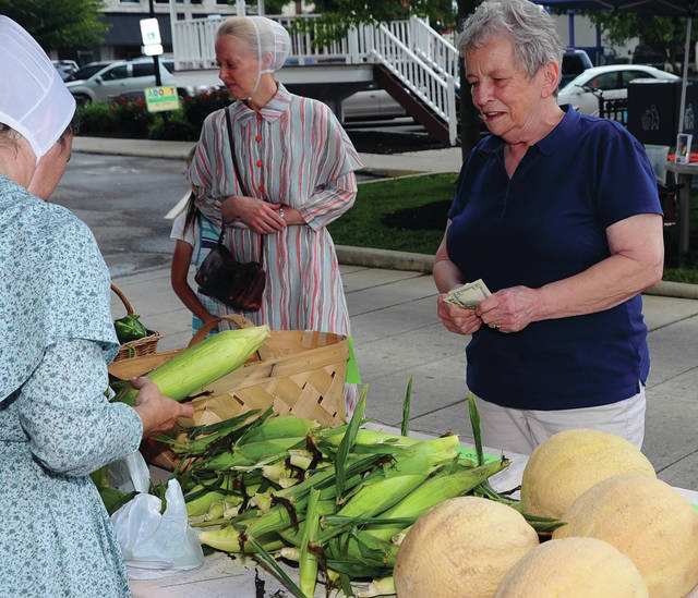 Mike Ullery   Daily Call Roxana Chesser of Piqua, right, purchases fresh sweet corn from Burns Produce of Piqua during the Mainstreet Piqua Farmer's Market on Thursday. Lorna Swisher, director of Mainstreet Piqua announced that Piqua Farmer's Market vendors are now able to accept Ohio Direction Card (Food Stamps) as payment for fresh produce and vegetables. Swisher said that the new payment option gives those who are on food stamp programs the option to shop the Market for fresh, locally-grown, and competitively-priced products. The Mainstreet Piqua Farmer's Market is held every Thursday thru Sept. 14, from 3:30 - 6:30 p.m.on High Street in front of the Piqua Public Library.