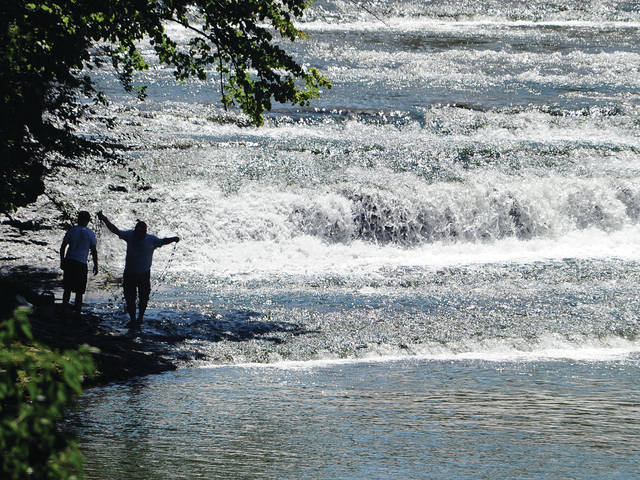 Mike Ullery | Daily Call A pair of anglers seine for minnows at the base of Greenville Falls near Covington on Saturday.