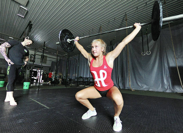 Anthony Weber | Troy Daily News Tipp City's Carson Culpepper performs several cleans while her coach, Josh Bunch, observes in the background at Practice CrossFit.