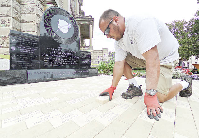 "Anthony Weber | Troy Daily News Tom Lillicrap places a laser cut brick at the Miami County Law Enforcement Memorial on Tuesday at Courthouse Plaza in Troy. Lillicrap Timber and Mulch of Piqua, who donated hours of work, completed a remodeling project, which included concrete work, metal edging and landscape this week at the sight of the memorial. President of Miami County Fraternal Order of Police Lodge No. 58, and 48-year law enforcement veteran, Billie Ray, said every brick down has been replaced with a lazer cut brick. He mentioned a brick can be made available for any active, retired or former Miami County law enforcement officer in good standing through application with the FOP Lodge No. 58. Ray said the work done in the project was taken care of through the Miami County FOP and wishes to thank Piqua Granite, who created the monument, Tom Lillicrap and his crew, as well as CD Solutions out of Pleasant Hill. ""The memorial is nice for the officers, survivors, community and the officers who go out here everyday and risk their life,"" Ray said. The memorial that was dedicated in the summer of 1999 is a lasting memorial to those law enforcement officers who have died in the line of duty."