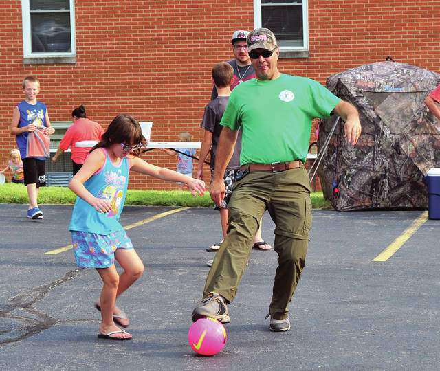 Mike Ullery | Daily Call Piqua firefighter Bob Bloom shows his skill at soccer as he kicks the ball around with Mary Hutton, 10, during a National Night Out event at Central Baptist Church in Shawnee on Tuesday evening. The event was just one of more than a dozen National Night Out locations in neighborhoods throughout the City of Piqua.
