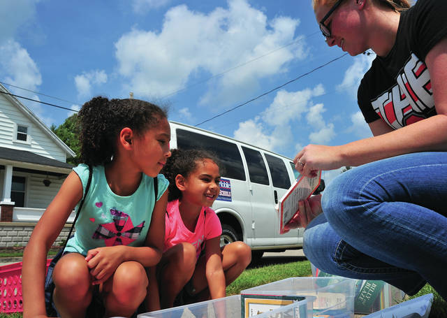 Mike Ullery | Daily Call Piqua City Schools teacher Kiley Taylor, right, helps Maliya Chambers, 7, and her sister Adrianna, 6, select books from the Piqua City Schools Book Mobile during a stop at Kiwanis Park on Thursday. Taylor, a graduate of Northmont High School is beginning her first year as a teacher. She will be at Piqua Central Intermediate School.