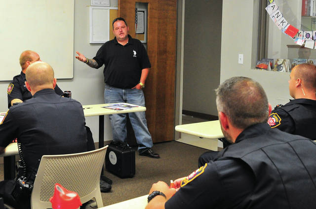 Mike Ullery | Daily Call Shawn Poling, a recovering drug addict who experienced a number of encounters with Piqua police officers during his years of addiction, meets with Piqua officers at the department on Wednesday evening. Poling, who now operates a drug rehabilitation facility in Florida, asked Piqua Chief of Police Bruce Jamison if he could meet with officers and apologize for past actions.