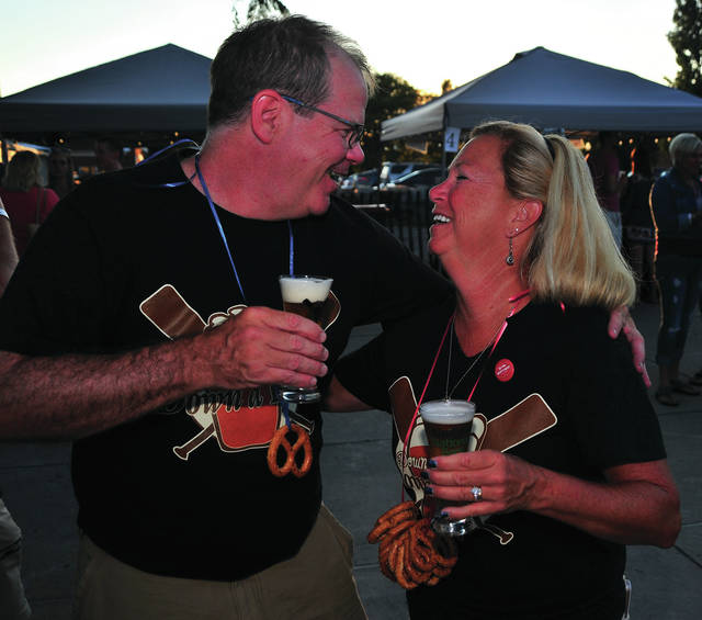 Mike Ullery | Daily Call Dr. Jim Burkhardt, aka Dr. Beer, and his wife Cheryl enjoy a happy moment together during the 2017 Down the River, Down a Beer event at Lock 9 Park on Saturday.