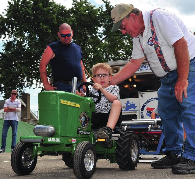 Mike Ullery | Daily Call Christopher Whitehead, 4, of Piqua, makes his way down the track at the Kiddie Tractor Pull on Monday at the Miami County Fair as pulling association member Pete Dietrich, right, urges him on.