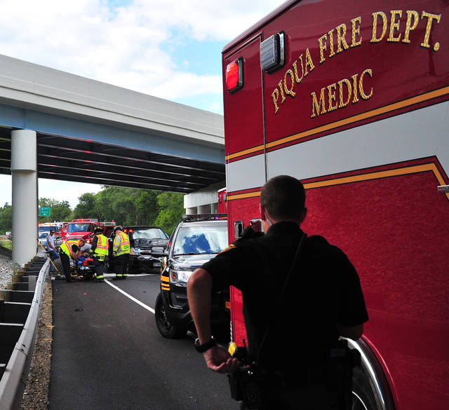 Mike Ullery | Daily Call Medics from Piqua Fire Department along with Covington Firefighters prepare a crash victim for transports following a two-vehicle crash on Co. Rd. 25-A at the I-75 Farrington Road interchange on Wednesday afternoon.