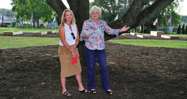 Mike Ullery | Daily Call Ruth Koon, right, and Anna Baumeister, the two coordinators of the school yard project, formally present the Garden Tribe School Yard Garden to Piqua City Schools and Piqua Catholic School. The presentation was held during ceremonies on the site of the former Nicklin Elementary School during a special Piqua Area Chamber of Commerce Business After Hours on Thursday.