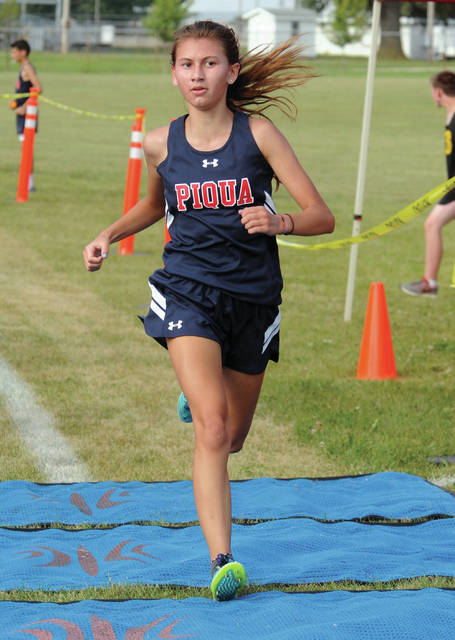 Mike Ullery | Daily Call Piqua's Maeve Vulcan crosses the finish line for a second-place finish in Wednesday's cross country race with Sidney.