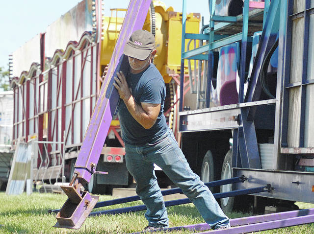 Anthony Weber | Troy Daily News A crew from Burton Brothers Amusements works on setting a tower for the Ferris wheel in preparation of the 2017 Miami County Fair Tuesday in Troy.