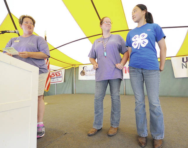Anthony Weber | Troy Daily News Jane Jess, left, recognizes Miami County Junior Fair officer Rylee Puthoff along with Yui Takahashi at the 2017 Miami County Fair. Puthoff is the first student from the county to participate in the Labo International program. She is hosting Yui Takahashi.
