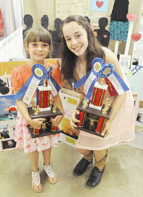 Anthony Weber | Troy Daily News Emma Sutherly, right, stands with her cousin, Josie Shane, who is modeling a dress Sutherly recently made. Sutherly is a member of Elizabeth Livestock 4-H Club.