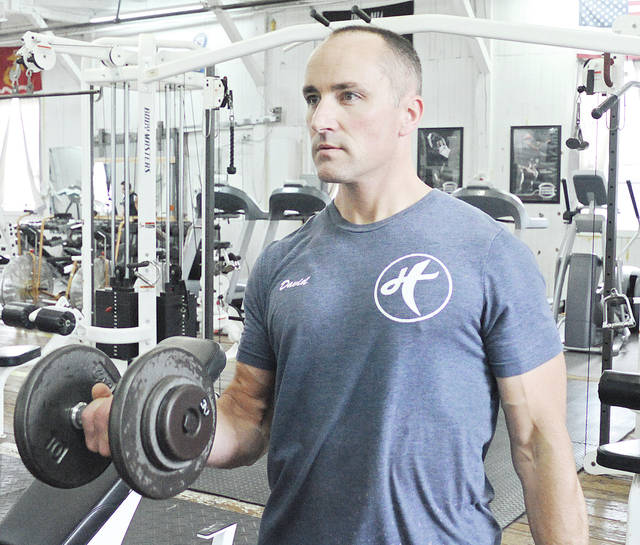 Anthony Weber | Aim Media Hybrid Strength and Fitness owner David Scott works on curls recently at his facility on Clay Street in Troy.