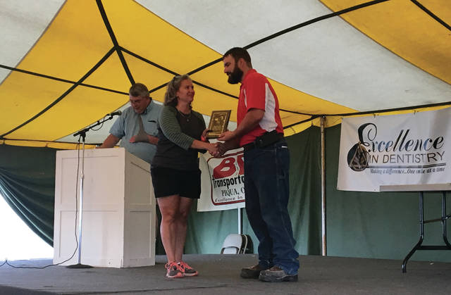 Sam Wildow | Daily Call Amber Weldy of Troy shakes hands with Nick Shellenberger after winning the Baker's Delight award during the Art and Horticulture Hall awards ceremony Sunday evening at the Miami County Fair.