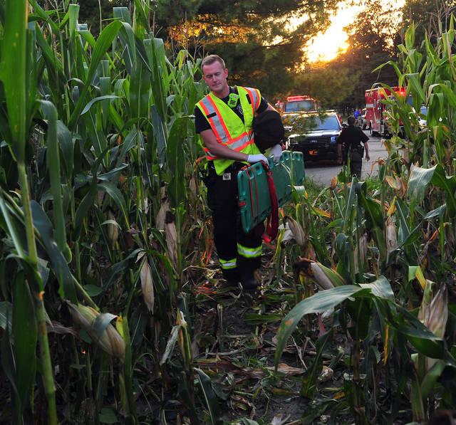 Mike Ullery | Daily Call Piqua medics and firefighters, along with Miami County Sheriff's Deputies and mutual aide firefighters from Fletcher work at the scene of a single-vehicle crash on Parker Drive, north of Piqua on Wednesday evening.