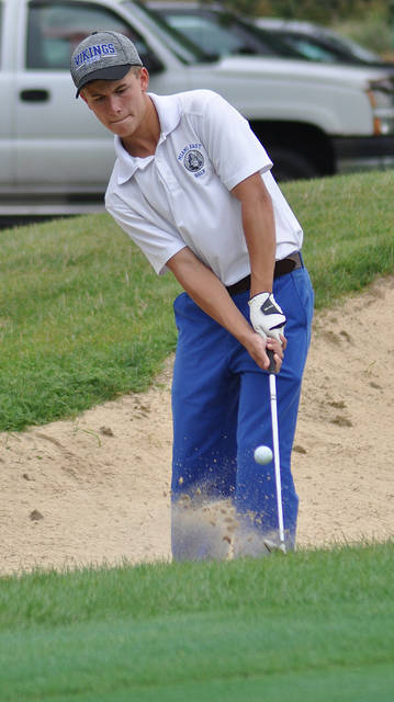 Rob Kiser/Call Photo Miami East's Zac Johnson hits out of a bunker on the ninth green Monday.