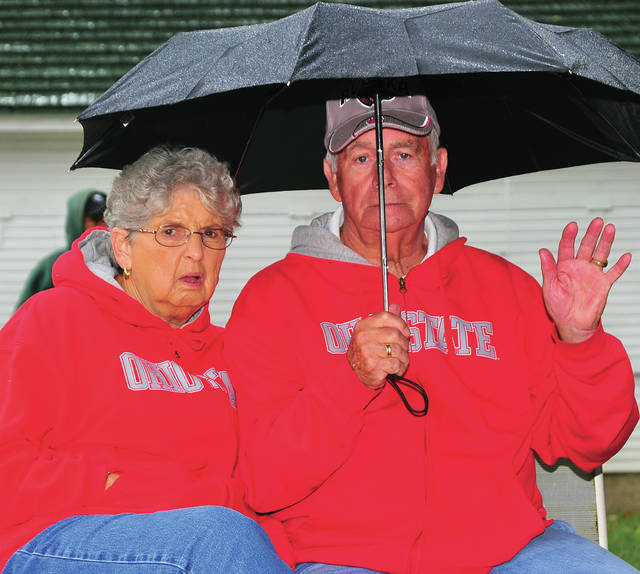 John and Marabele Garland of Greenville don't let a little rain dampen their enthusiasm for the entertainment at Fort Rowdy Days on Saturday.