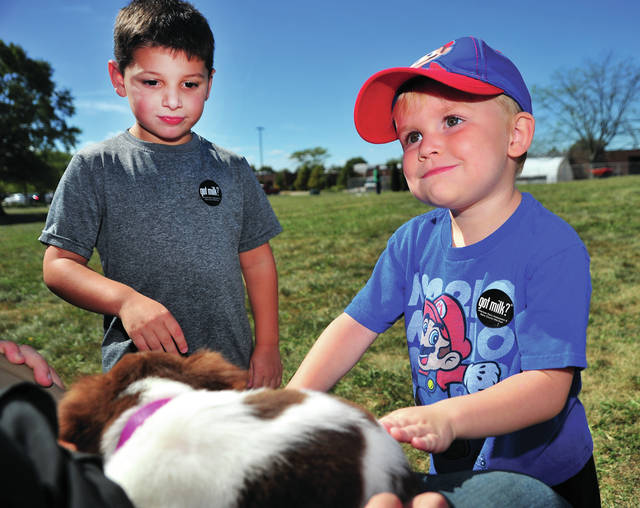 Mike Ullery | Daily Call Tate Andrews, left, and Isaac DeBrosse, of Piqua, are introduced to a puppy at the Upper Valley Career Center on Thursday. The four-year-olds attend the career centers Early Childhood Development Program.