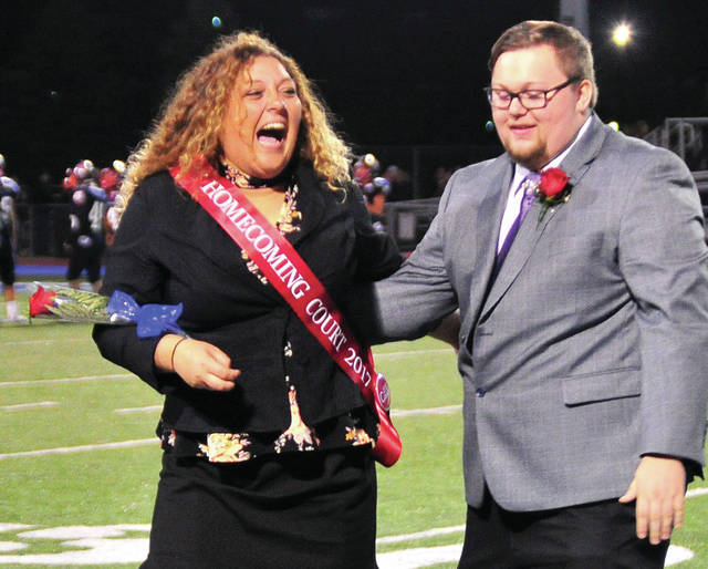 Mike Ullery | Daily Call A'zeh Johnson, left, reacts to being announced as Piqua High School Homecoming Queen for 2017 during Friday's game against Sidney. With her is her escort Ryan Pierre. Homecoming king will be crowned during tonight's homecoming dance at the high school.