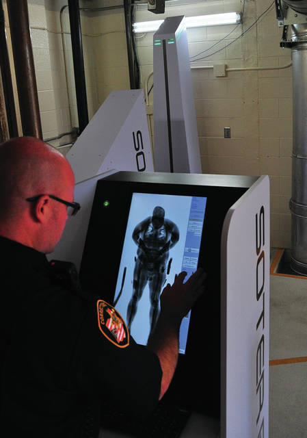 Mike Ullery | Daily Call Miami County Corrections Officer Ryan Carson domonstrates the new full-body scanner that is being readied for use at the Miami County Jail.