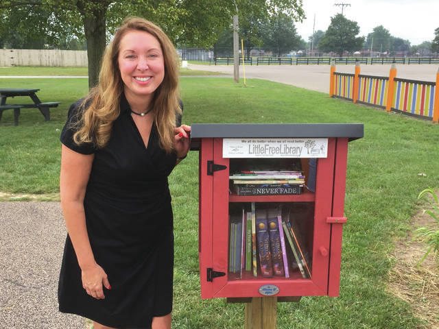 Provided photo Kathy Alexander poses next to the Little Free Library that was installed recently in Pitsenbarger Park. This literacy project is in memory of her late son, Clifton, an avid reader. Plans are in the works to add more Little Free Libraries around Piqua and Shawnee.