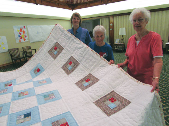 "First United Church of Christ members Jane Percel, Sharon Cooper and Betty Burt, show off the women's fellowship quilt called ""Windows of Hope."" The queen-sized quilt will be raffled off on Nov. 5. Proceeds will benefit Miami County Recovery Council."