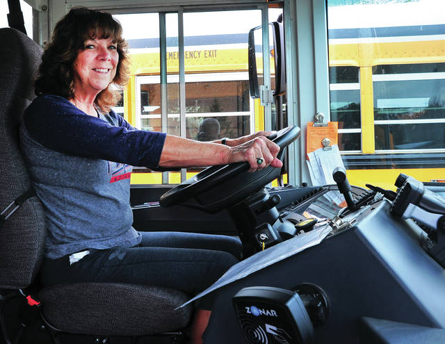 Mike Ullery | Daily Call Piqua City Schools bus driver Cheryl Jones waits on students to board her bus at Piqua Junior High on Wednesday. Jones has been driving bus for more than 25 years. Like many districts across the nation, PCS is experiencing a shortage of qualified school bus drivers.