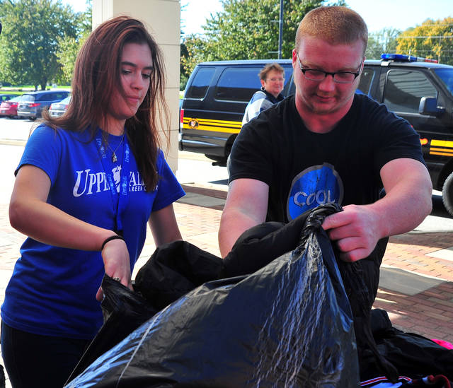 Mike Ullery   Daily Call Makenzie Ranley, left, and Kurt Stonerock sort coats to be loaded into Miami County Sheriff's Office vehicles for distribution to those in need as part of the 2017 Operation Cover Up campaign at Upper Valley Career Center on Friday. Ranley, a senior from Ft. Loramie, personally collected 75 coats during the campaign. Stonerock is a student from Houston.