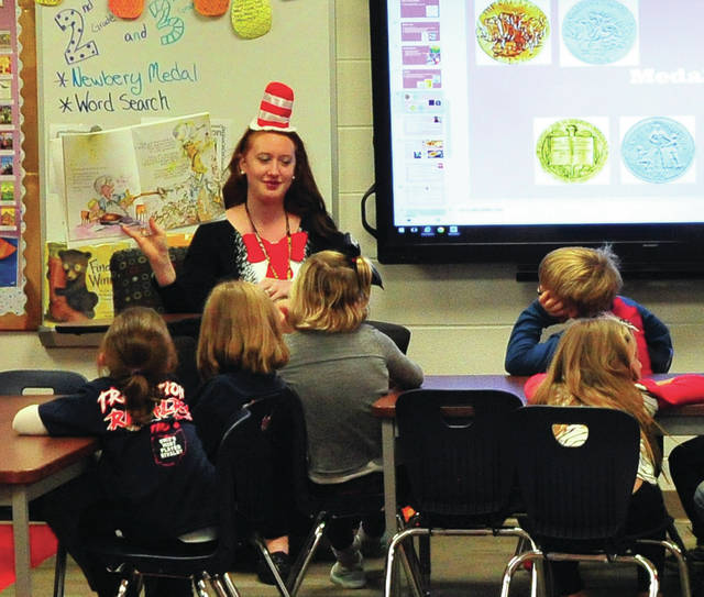 Mike Ullery | Daily Call The Cat in the Hat, aka, Springcreek librarian Abby Everett, reads with students at the school last week. Everett and other staff members dressed as their favorite book characters to promote reading.
