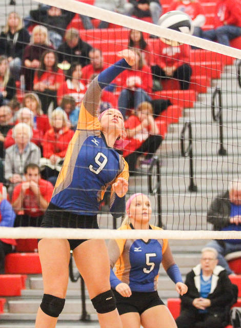 Russia's Laurissa Poling spikes the ball over the net during a Division IV district final on Saturday against Riverside at the Trojan Activities Center. Russia won in three sets to capture its first district crown in 14 years.