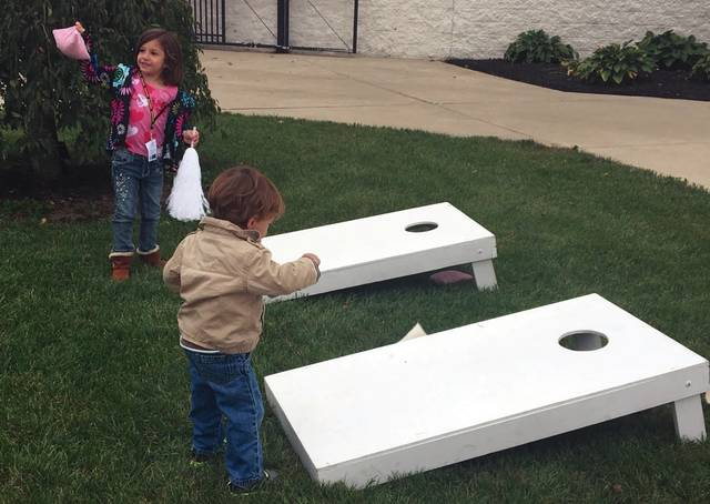 Sam Wildow | Daily Call Alexis Stein, 5, and Evan Stein, 2, play corn hole at the Piqua Area Chamber of Commerce's Thursday Night Lights tailgate party at Alexander Stadium on Thursday evening.