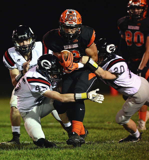 Ben Robinson/GoBuccs.com Bradford's Hunter Penkal is tackled by Kadin Presser (45) and Brayden Wiggins Friday night.