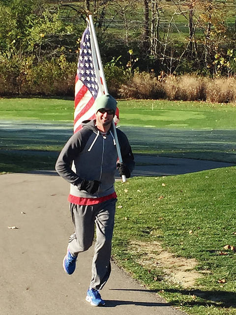 Photo Provided Jeff Bradley runs with the American flag during last year's Wounded Warrior 5K walk/run at Echo Hills