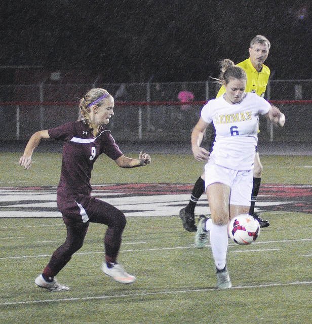 Rob Kiser/Call Photo Lehman Catholic's Grace Monnin sends the ball down the field as Urbana's Sam Tracy closes in Monday night at Franklin.