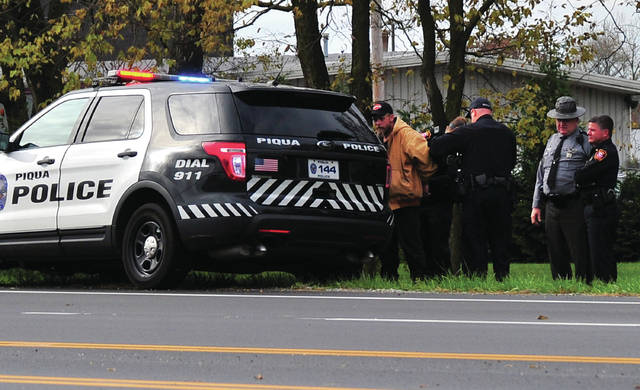 Mike Ullery | Daily Call Piqua police, with assistance from Ohio State Highway Patrol troopers, take Marcus Turnbill, 45, of Piqua into custody in connection to a Thursday morning theft from the Piqua Elder-Beerman store after he was stopped on County Road 25-A near Eldean Road less than a half-hour after the alleged theft occurred.