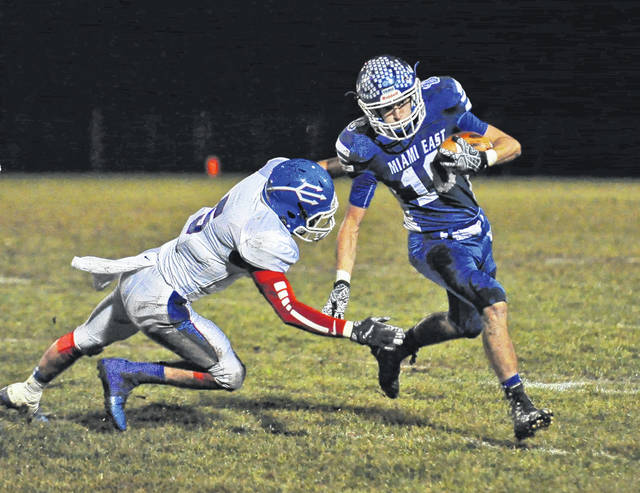 Josh Brown/Troy Daily News Miami East's Justin Brown avoids a Reading tackler during a first-round playoff game Friday night.