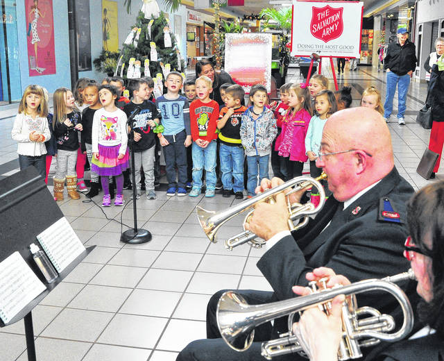 Mike Ullery | Daily Call Preschoolers from Greene Street United Methodist Daycare sing Christmas carols accompanied by the Piqua Salvation Army Band at the Miami Valley Centre Mall on Thursday as the Christmas Bell-ringing season and Angel Tree were officially opened.
