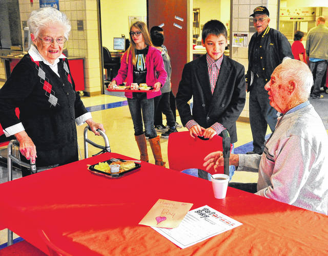 Mike Ullery | Daily Call United States Army veteran, Lewis Marrs, seated, and his wife Joan, left, are served breakfast by their grandson Wyatt, at 6th grader at Piqua Central Intermediate School during the annual Serving Those Who Served event on Friday.