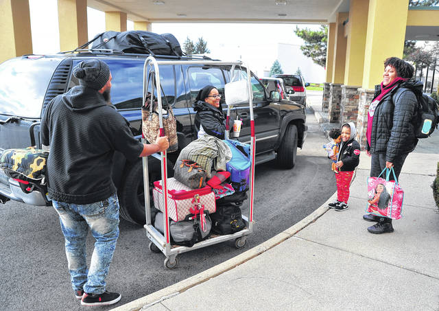 Cameron Mathis, left, and his family, Brittany Dangerfield, Maxine Blair-Quamina, kids Harley, 3, and Memphis, 6 months, unload luggage at the Comfort Inn at the Miami Valley Centre Mall on Wednesday. The family lives in Cleveland but travels home every year to spend Thanksgiving with family. They are one of thousands of families traveling out of town to celebrate Thanksgiving
