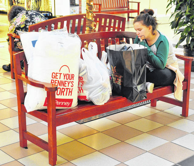 Mike Ullery | Daily Call Sierra Leonard, 11, of Piqua checks her phone while guarding the morning shopping packages at the Miami Valley Centre Mall on Friday morning.