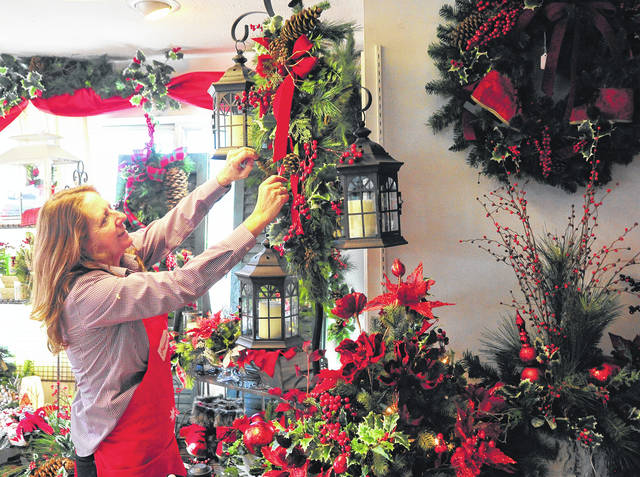 Mike Ullery | Daily Call Kim Hampshire of Genell's Flower Shop in Piqua makes some adjustments on one of some 64 floral lanterns that are to be a part of the holiday concert at Piqua High School on Sunday, Dec. 10.