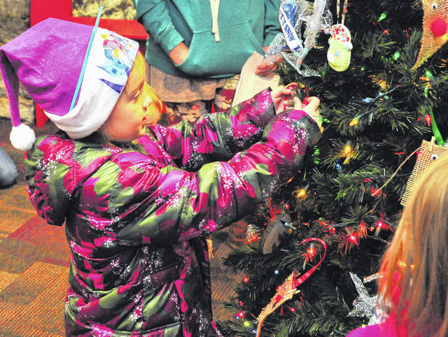 Mike Ullery | Daily Call Lucy Whalen, 5, of Daisy Troop 20520 in Piqua places her ornament on the Christmas Tree in the Children's Area of the Piqua Public Library during a Brownie/Girl Scout event on Wednesday.