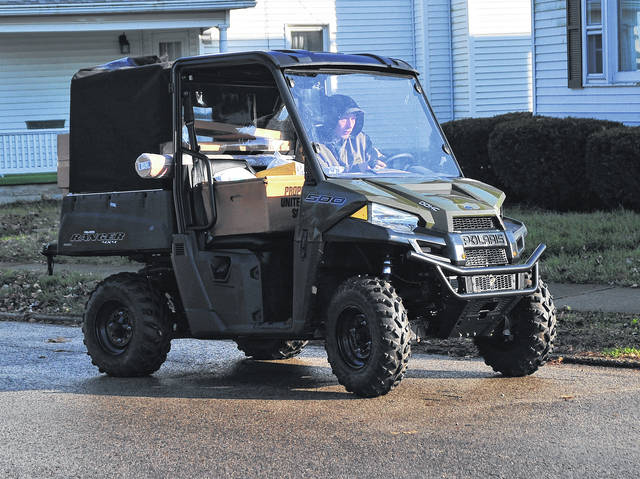 Mike Ullery   Daily Call A United States Postal Service worker utilizes an ATV to deliver parcels along South Street in Piqua on Thursday afternoon.