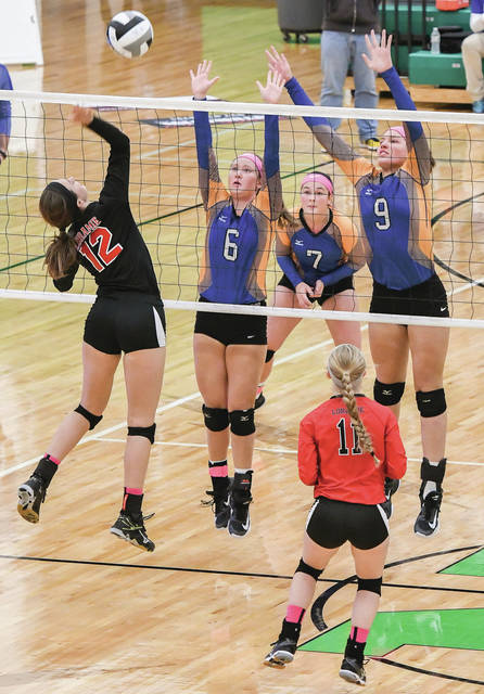 Russia's Jenna Cordonnier (left middle), Faith Apple (middle) and Laurissa Poling (top right attempt to defend the spike from Fort Loramie's Chloe Stang (left) during a Division IV regional semifinal on Thursday.