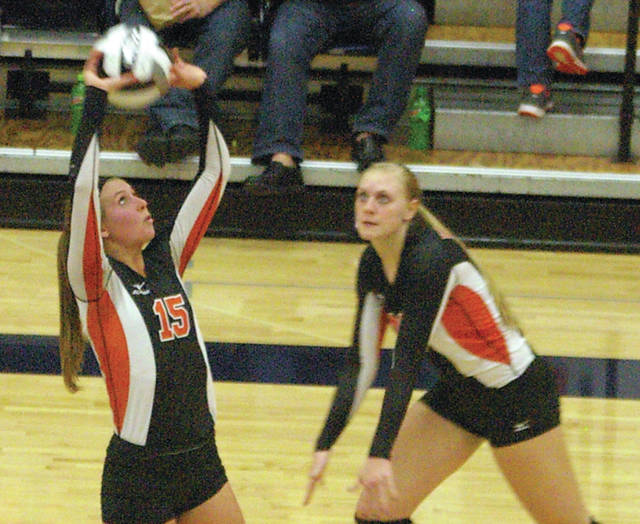 Kyle Shaner/Daily Advocate Versailles' Ellen Peters sets the ball Thursday against Johnstown-Monroe at Trent Arena.