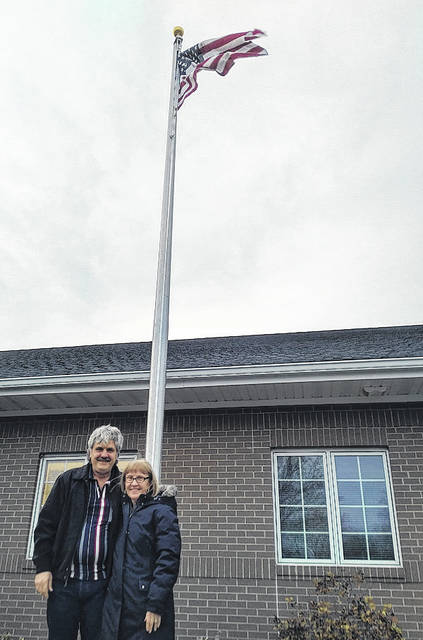 Provided photo Eddie Tucker and JoAnn Barhorst pose outside with the new pole and flag at Health Partners of Miami County.