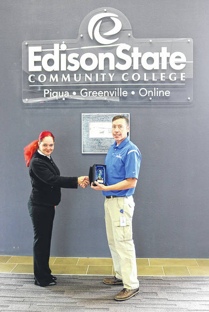 Provided photo Rachel Redmon, program manager for Charitable Recycling, presents Jason Evans, IT Help Desk supervisor, with a trophy for charitable equipment contributions made on behalf of Edison State Community College.